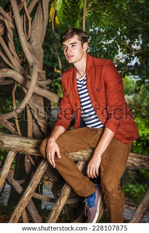 Thinking Outside. Wearing a dark reddish brown jacket, unbuttoned, striped under shit, brown corduroy pants, a young handsome guy is sitting on a wooden fence with rattan trees, lost in thought. - stock photo