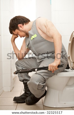 Thinking plumber with the adjustable wrench in the bathroom.