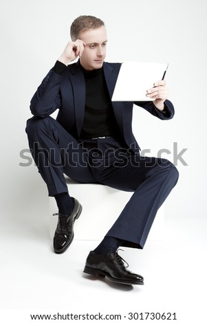 Thinking Portrait of Handsome Man with Digital Tablet Sitting. Vertical Image Composition Sitting. Vertical Image Composition