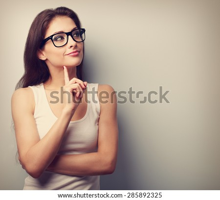 Thinking professional woman in glasses looking with finger under the face on empty space background. Vintage portrait - stock photo