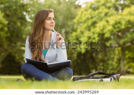 Thinking student sitting and holding book in park at school