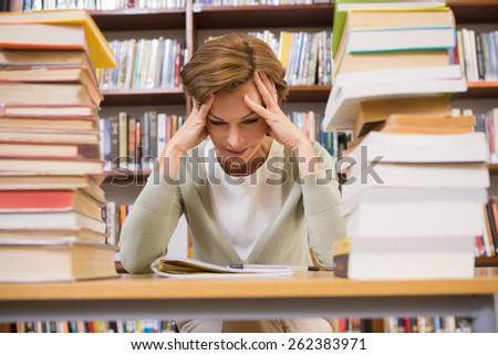 Thinking teacher sitting at desk at elementary school - stock photo