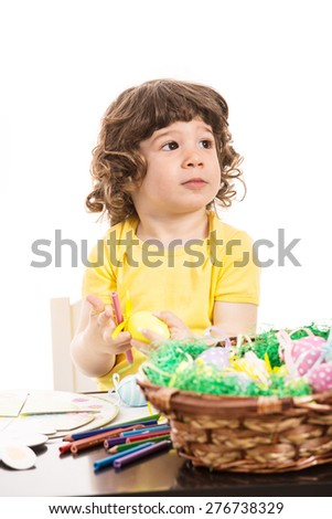 Thinking toddler boy looking away and sitting at table with Easter eggs - stock photo