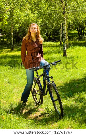 Thinking woman on bicycle in the spring forest - stock photo