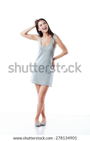 Thinking woman standing in full length isolated on white background in grey neutral dress. Mixed asian / caucasian young woman. - stock photo