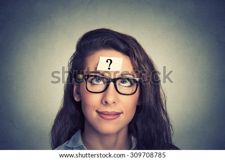 thinking woman with question mark on gray wall background - stock photo