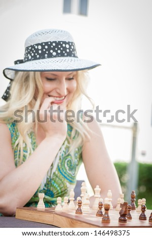 Thinking woman with straw hat in a chess game - stock photo