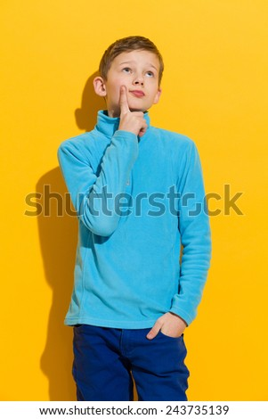 Thinking young boy standing and holding index finger on a chin. Three quarter length length studio shot on yellow background. - stock photo