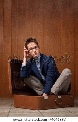 Thinking young Caucasian man sits inside a suitcase