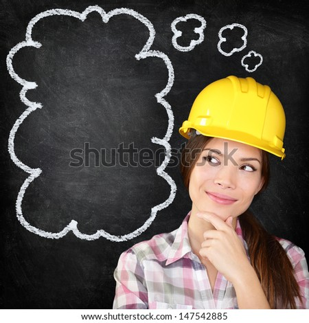 Thinking young female construction worker, architect, engineer, surveyor wearing hardhat on blackboard thinking with hand to chin looking to the thinking bubble on chalkboard texture. - stock photo