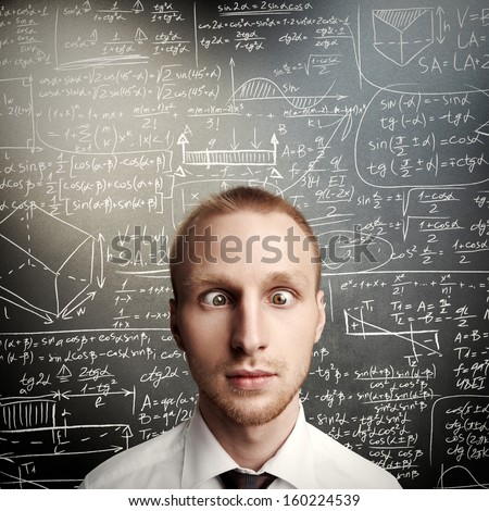 thinking young man against desk with formulas - stock photo