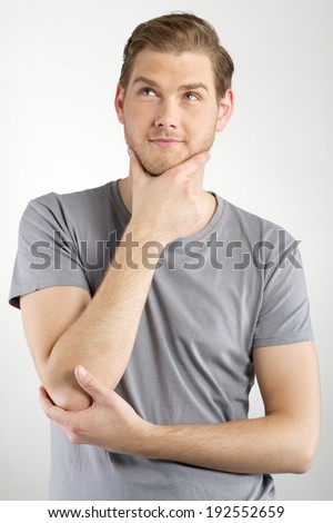 Thinking young man isolated on light background - stock photo