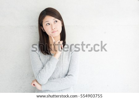 Thinking young woman against concrete wall