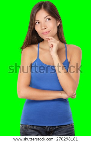 Thinking young woman looking at copy space. Beautiful pensive mixed race Caucasian / Chinese Asian girl isolated on green background in blue tank top. - stock photo