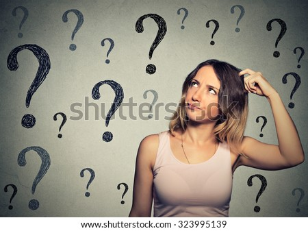 Thinking young woman with looking up at many questions mark isolated on gray wall background - stock photo
