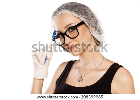 thinking young woman with pen, protective cap and gloves - stock photo