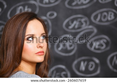 Thinking young woman with yes or no choice on grey background - stock photo