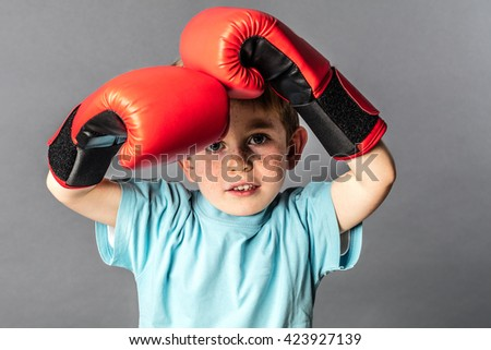 thinking young 5-year old boy with big boxing gloves protecting his face to fight or defend himself, grey background studio
