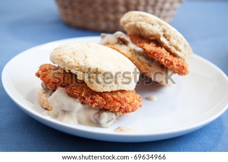 Thinly sliced crispy fried chicken with creamy gravy and mushrooms on a fluffy biscuit - stock photo