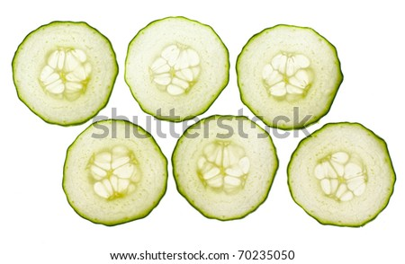 Thinly sliced pieces of cucumber lit from behind - stock photo