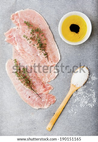 thinly sliced raw meat , thyme, olive oil, balsamic vinegar , red onion and salt. pork fillet on the baking paper and a dark background. cooking ingredients. pig.  - stock photo