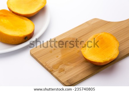 Third of a ripe mango and its juice on a wooden cutting board. The remaining two thirds placed on a plate. Deep yellow fruit pulp in tangerine peel. Medium DOF. Photographed on white background. - stock photo