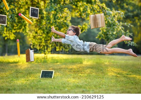 Thirst for knowledge, flying cute little boy - stock photo