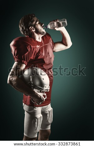 Thirsty American football player in red jersey drinking water against green background with vignette