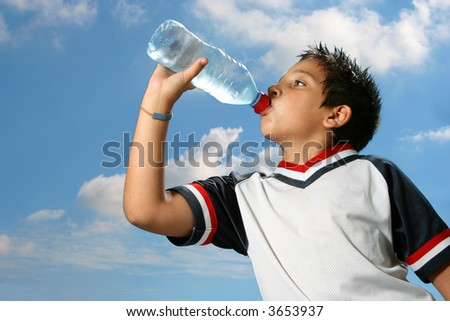 Thirsty boy drinking fresh water outdoors wearing sport clothes - stock photo