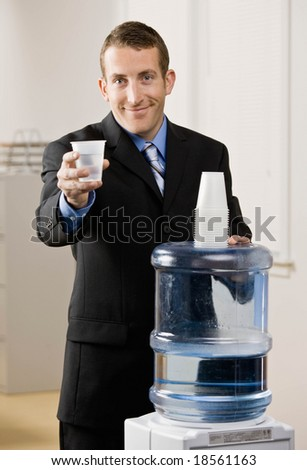 Thirsty businessman filling cup from water cooler - stock photo