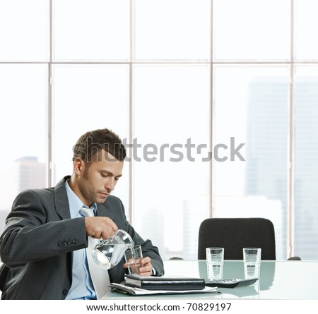 Thirsty businessman sitting at meeting table pouring water from jug into glass to drink in meeting break. - stock photo