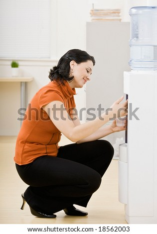 Thirsty businesswoman kneeling and filling glass of water at water cooler