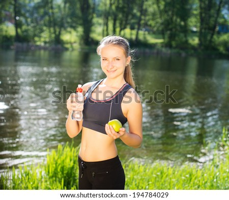 Thirsty girl resting taking a break with bottle of water and apple outside after training.  - stock photo