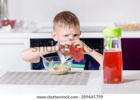 Thirsty little boy drinking fruit juice in a kitchen peering over the top of the glass with a serious expression - stock photo
