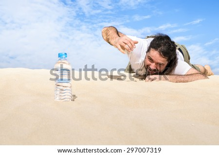 Thirsty man in the desert reaches for a bottle of pure water  - stock photo