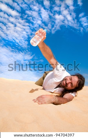 Thirsty man in the desert with a bottle of water