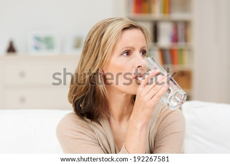 Thirsty woman drinking a refreshing healthy glass of cold fresh water as she sits on a couch at home staring into the distance with a serious expression - stock photo