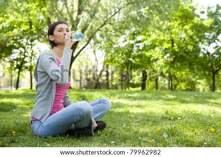thirsty woman sitting on grass in park with bottle of water