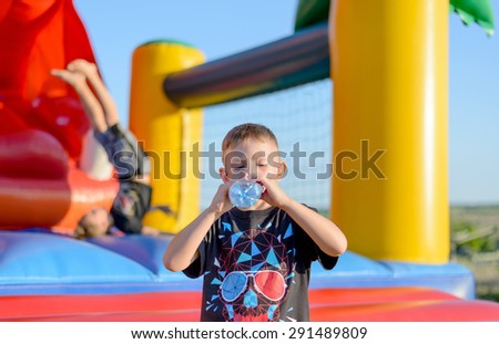 Thirsty young boy drinking bottled water after playing on colorful plastic equipment at a funfair or childrens playground - stock photo
