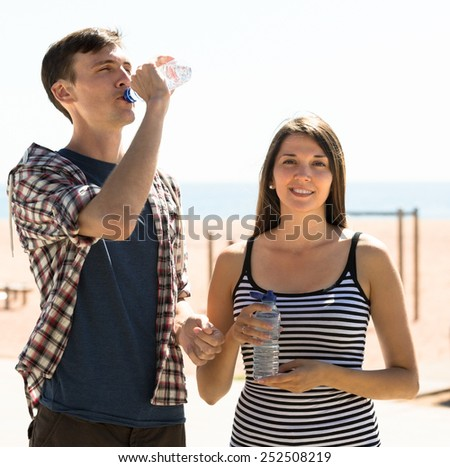 Thirsty young couple drinking water from bottle at sunny day - stock photo