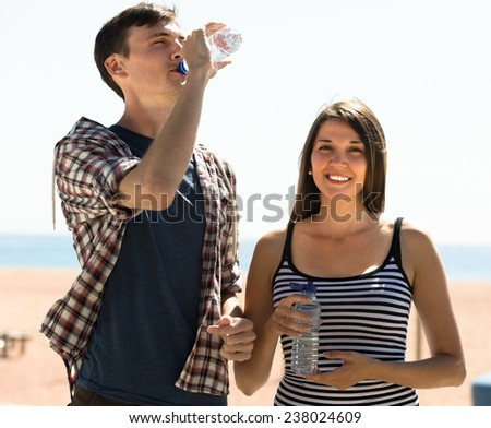 Thirsty young couple taking a refreshing drink of water at sunny day - stock photo