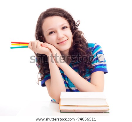 thirteen year old schoolgirl sitting by the table with pens and books, isolated against white background - stock photo