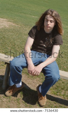 thirteen year old teen sulking as though isolated from school friends - stock photo