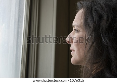 Thirty-eight year old impoverished woman looking out window of low income home.