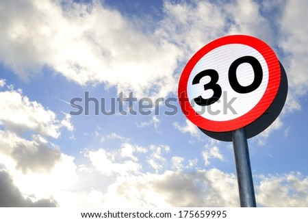 Thirty mile per hour street sign with dramatic clouds in background.