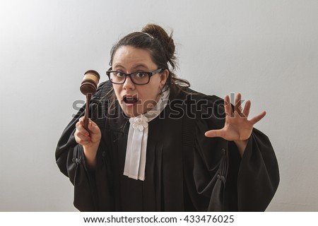 thirty something brunette woman wearing a canadian lawyer toga with a gavel in her hands
