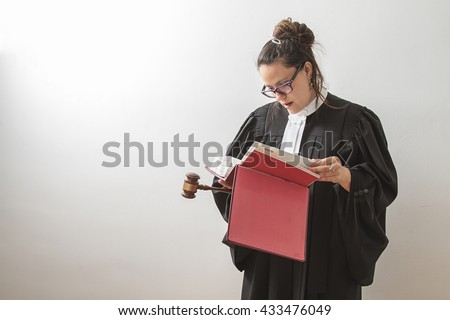 thirty something brunette woman wearing a canadian lawyer toga with a gavel in her hands and reading a red criminal law book