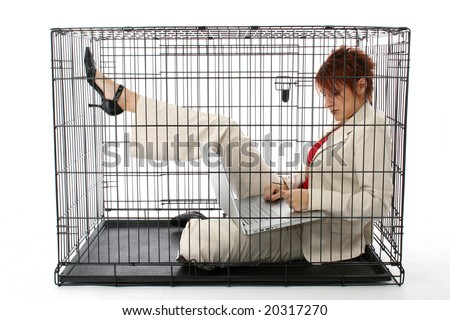 Thirty something business woman trapped in cage. - stock photo