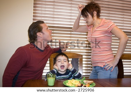 Thirty something couple at home fighting with upset son between them. - stock photo