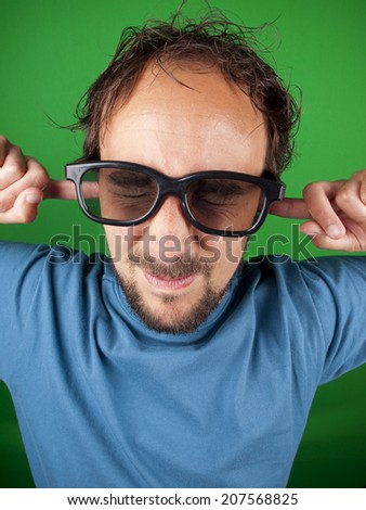 Thirty year old man with 3d glasses is too afraid to watch the movie over a green background - stock photo